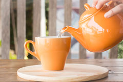 Hot tea is poured from teapot into a cup Royalty Free Stock Photo