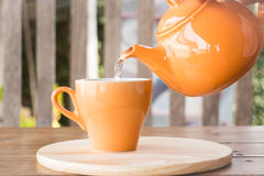 Hot tea is poured from teapot into a cup Royalty Free Stock Photography