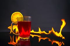 Hot tea in a red. Fireplace as background. Christmas or winter warming drink. stock photos