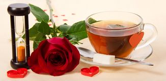 Hot tea, red rose and hourglasses Royalty Free Stock Images