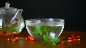 Hot tea from ripe red goji berries in a glass teapot
