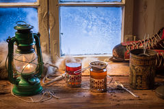 Hot tea in a small house at winter. On old wooden table Royalty Free Stock Photo
