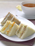 Hot tea and snack. A variety of club sandwiches served in a white plate with a cup of hot tea stock photography