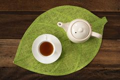 Hot tea and teapot on a table background. Hot tea and teapot on leaf shape mat Royalty Free Stock Photo