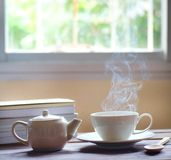 Hot tea and teapot on wooden table, window background, royalty free stock photos