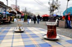 Hot tea in turkish small glass. Photo of Bit Pazar (Skopje) through a traditional tea glass Royalty Free Stock Photos