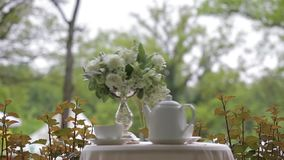 Hot tea in white cups and white teapot served outdoors on a white table decorated with a bouquet of flowers. Focus. Hot tea in white cups and white teapot served stock footage
