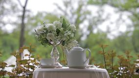 Hot tea in white cups and white teapot served outdoors on a white table decorated with a bouquet of beautiful flowers. Hot tea in white cups and white teapot stock video footage