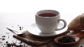 Hot tea on wooden table. A cup of hot tea is placed on a wooden table with dried tea leaves placed on a wooden spoon stock video