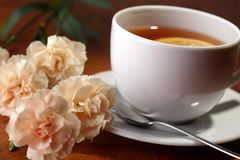 Hot teacup with lemon and flowers Stock Images