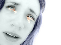 Hot tears in girl's sad eyes. A cold toned picture with greenish colours on a caucasian girl's face. Her tears are coloured orange and her mouth is slightly open royalty free stock photos