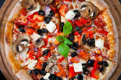 Hot testy pizza with tomatoes, mozzarella, mushrooms, olives, re. D pepper and basil on black concrete background. Copyspace. Top view. Banner Stock Images