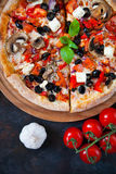 Hot testy pizza with tomatoes, mozzarella, mushrooms, olives, re. D pepper and basil on black concrete background. Copyspace. Top view. Banner Stock Photos