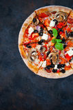 Hot testy pizza with tomatoes, mozzarella, mushrooms, olives, re. D pepper and basil on black concrete background. Copyspace. Top view. Banner Royalty Free Stock Photos