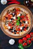 Hot testy pizza with tomatoes, mozzarella, mushrooms, olives, re. D pepper and basil on black concrete background. Copyspace. Top view. Banner Stock Photography