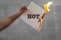 Hot text on fire on the paper. In hand royalty free stock photography