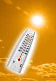 Hot thermometer  on orange sky. Thermometer on orange sky with sun and lens flare Stock Photography