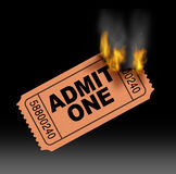 Hot Ticket. Entertainment concept with a best selling admit one paper entrance stub burning in flames with fire and smoke  as a symbol of very popular in demand Stock Photo