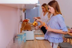 Teenage sister wearing blue blouse touching hot toast in the morning. Hot toast. Teenage sister wearing blue blouse and orange bracelet touching hot toast in the stock images