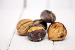 Hot toasted chestnuts on white wooden background. Close up view of some delicious hot toasted chestnuts on white wooden background Royalty Free Stock Photo