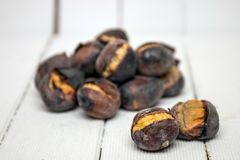Hot toasted chestnuts on white wooden background. Close up view of some delicious hot toasted chestnuts on white wooden background Stock Photos