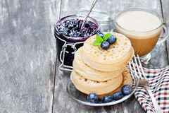 Hot  toasted  crumpets on the wooden table with blueberries and j Royalty Free Stock Image