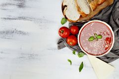 Tomato Soup with Parmesan cheese and Basil Leaves. Hot tomato soup with Parmesan cheese and basil leaves. Image shot from above in flat lay style Royalty Free Stock Photo