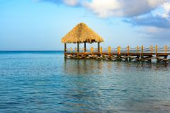 Hot tropical day the Caribbean sea pier with pergola. Palm leaves royalty free stock photo