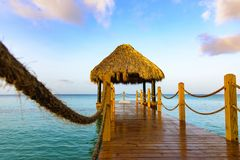Hot tropical day the Caribbean sea pier with pergola. Palm leaves stock image
