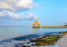 Hot tropical day the Caribbean sea pier with pergola. Palm leaves stock photos