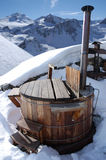 Hot tub. Wooden hot tub in the alps with mountains behind stock photos