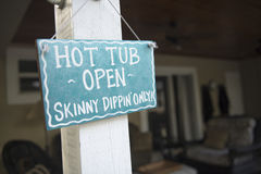 Hot Tub Open! a wooden sign at a vacation house in. Skinny dippin only! A sign next to a hot tub stock photo