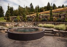 Modern backyard design with custom hot tub. A well designed terraced backyard in the Pacific Northwest features a custom stone and tile hot tub that resembles a Stock Photos