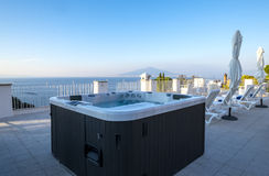 Hot Tub in a Resort Roof Top Overlooking Mount Vesuvius and the Mediterranean Sea. Hot Tub in a Resort Roof Top Overlooking the Mediterranean Sea and Mount Stock Photo