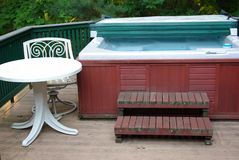 Hot tub with table. Hot tub with steps and a table and chair on a deck Royalty Free Stock Image