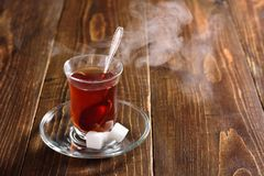 Hot Turkish tea with steam. Hot Turkish tea in glass with steam on wooden background stock image