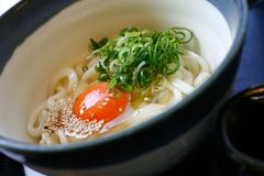Hot Udon in Broth. Hot Udon noodle in Broth, aka Kake Udon, with a raw egg, a typical Japanese breakfast Stock Image