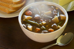 Hot vegetable beef soup. Bowl of vegetable beef soup with spoon and bread and butter on a dinner table stock images