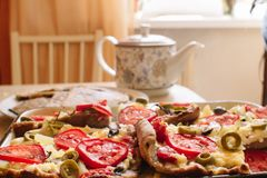 Hot vegetarian pizza over which steam from mozzarella cheese, tomatoes and olives royalty free stock photography