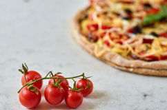 Hot vegetarian pizza with tomatoes, bell pepper, onion, black olives, cheese and spices on blurred white background close up Stock Images