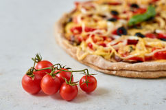 Hot vegetarian pizza with tomatoes, bell pepper, onion, black olives, cheese, spices on blurred white background close up Stock Images