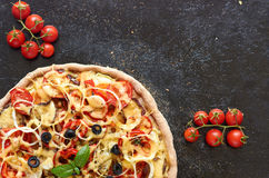 Hot vegetarian pizza with tomatoes, bell pepper, onion, olives, cheese, spices on dark baking tray background with copy space. Hot vegetarian pizza with tomatoes Stock Photo