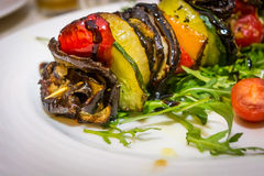 Hot vegetarian shashlik. With courgette, aubergine, onion, red pepper and arugula royalty free stock photography
