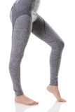Hot view of fit sexy woman legs from side in gray sports thermal underwear with pattern. Stock Photos