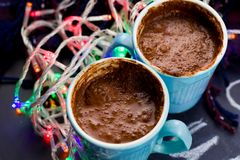 Hot warming chocolate. Hot chocolate and garland lights on the table stock image