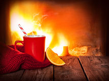 Hot warming drink in a red mug, orange slice and fireplace. Hot drink in a red mug and orange slice on vintage wood table. Fireplace as background. Christmas or stock photography