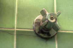 Hot water. Faucet on green shower tiles Stock Photos