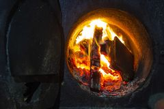 Hot water boiler with open door and fire inside and scoop with coal royalty free stock images
