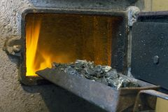 Hot water boiler with open door and fire inside and scoop with coal stock photo