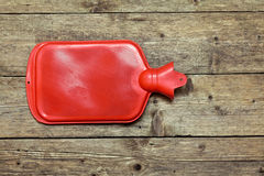 Hot water bottle. Or bag on wooden background Royalty Free Stock Photos